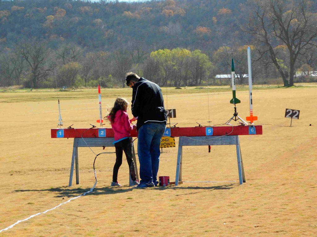 Dad helping daughter load a rocket